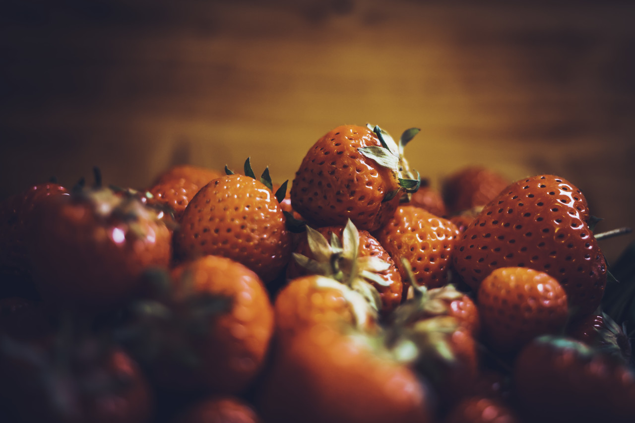 red strawberries wood background