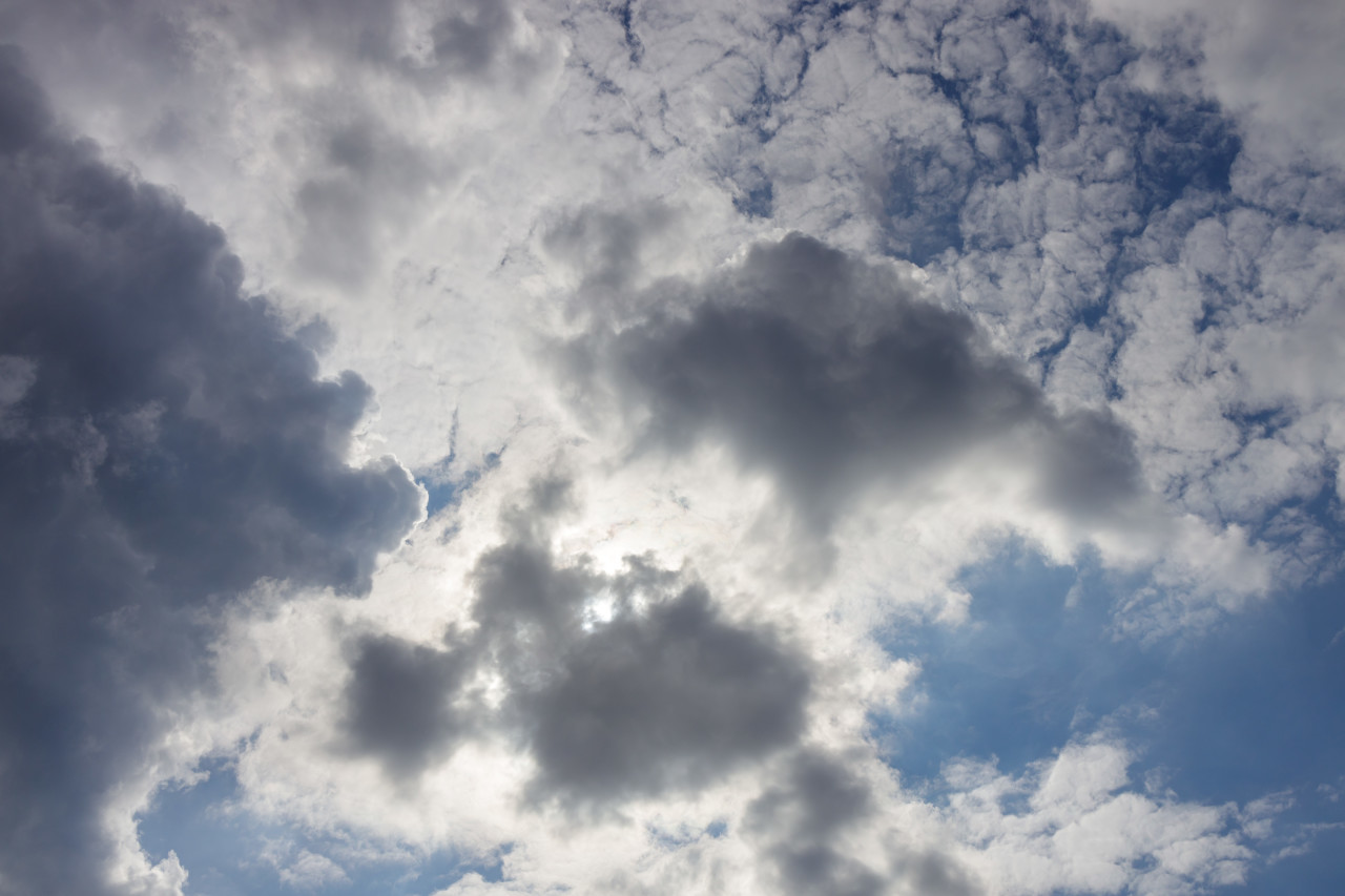 Sun behind white Clouds on a blue Sky for sky replacement