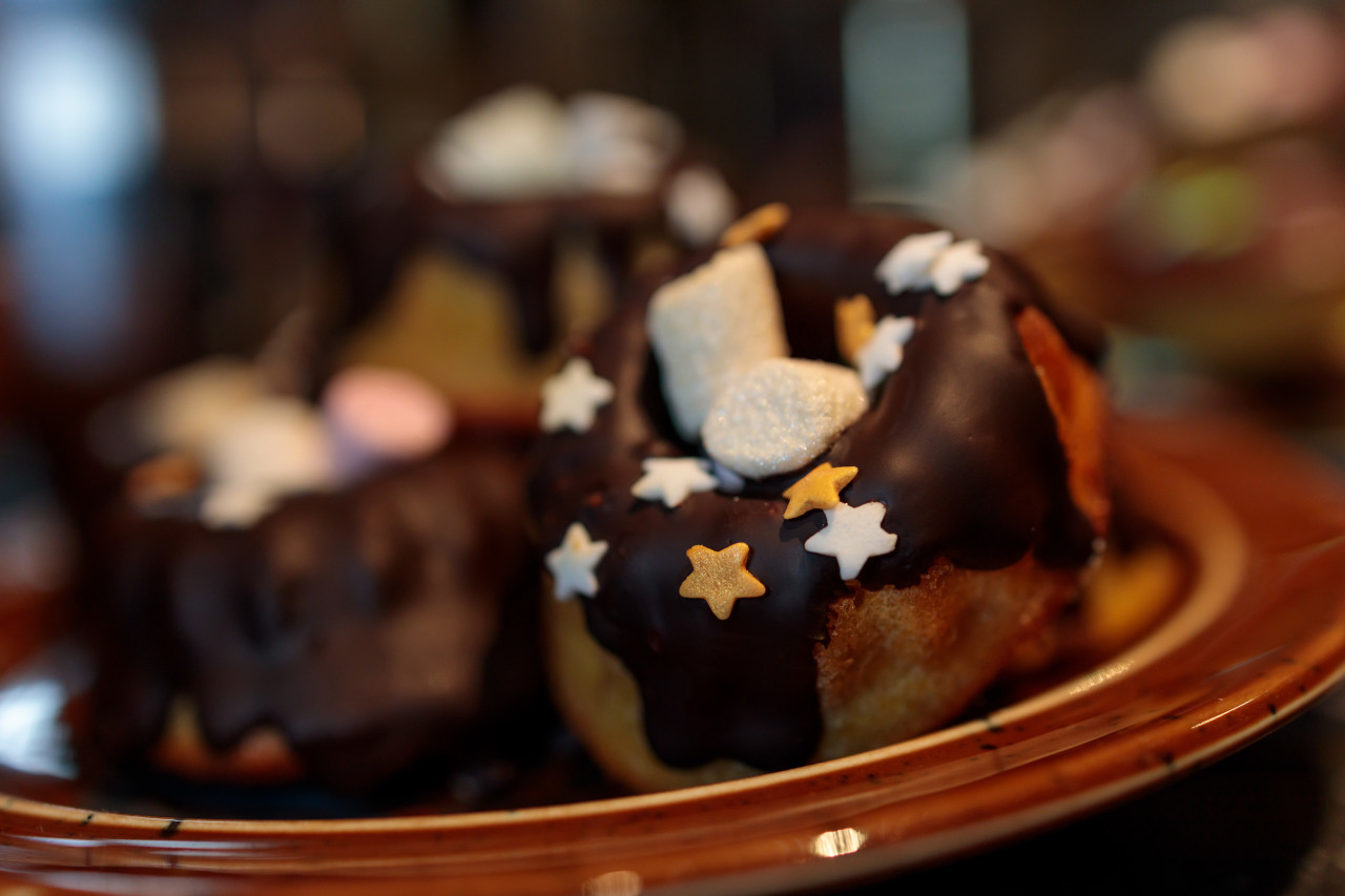Small chocolate Cakes decorated with colored sugar stars and marshmallows