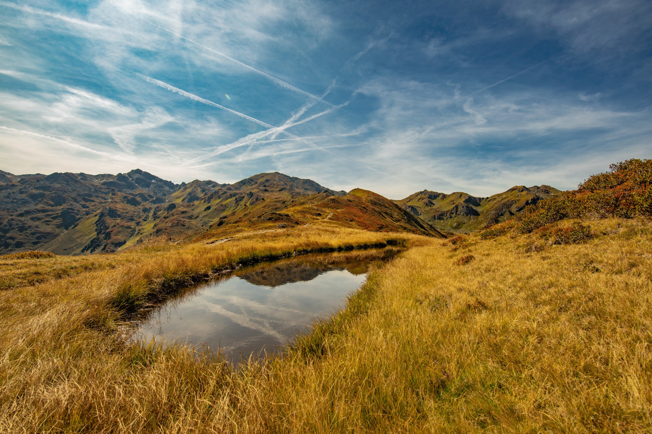 Landscape panorama of the Austrian Alps with a small waterhole