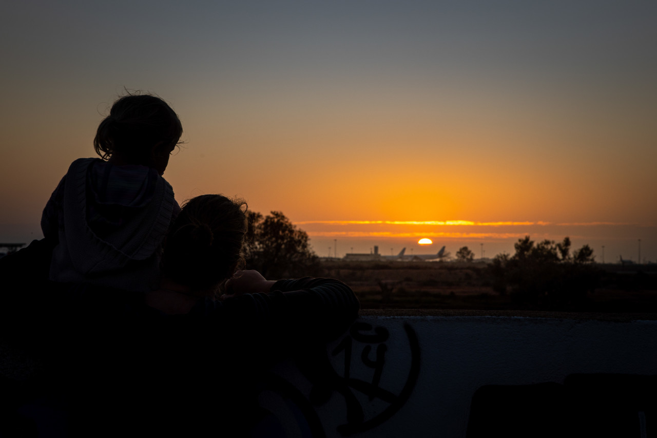 Mother and daughter watch the sunset on the beach