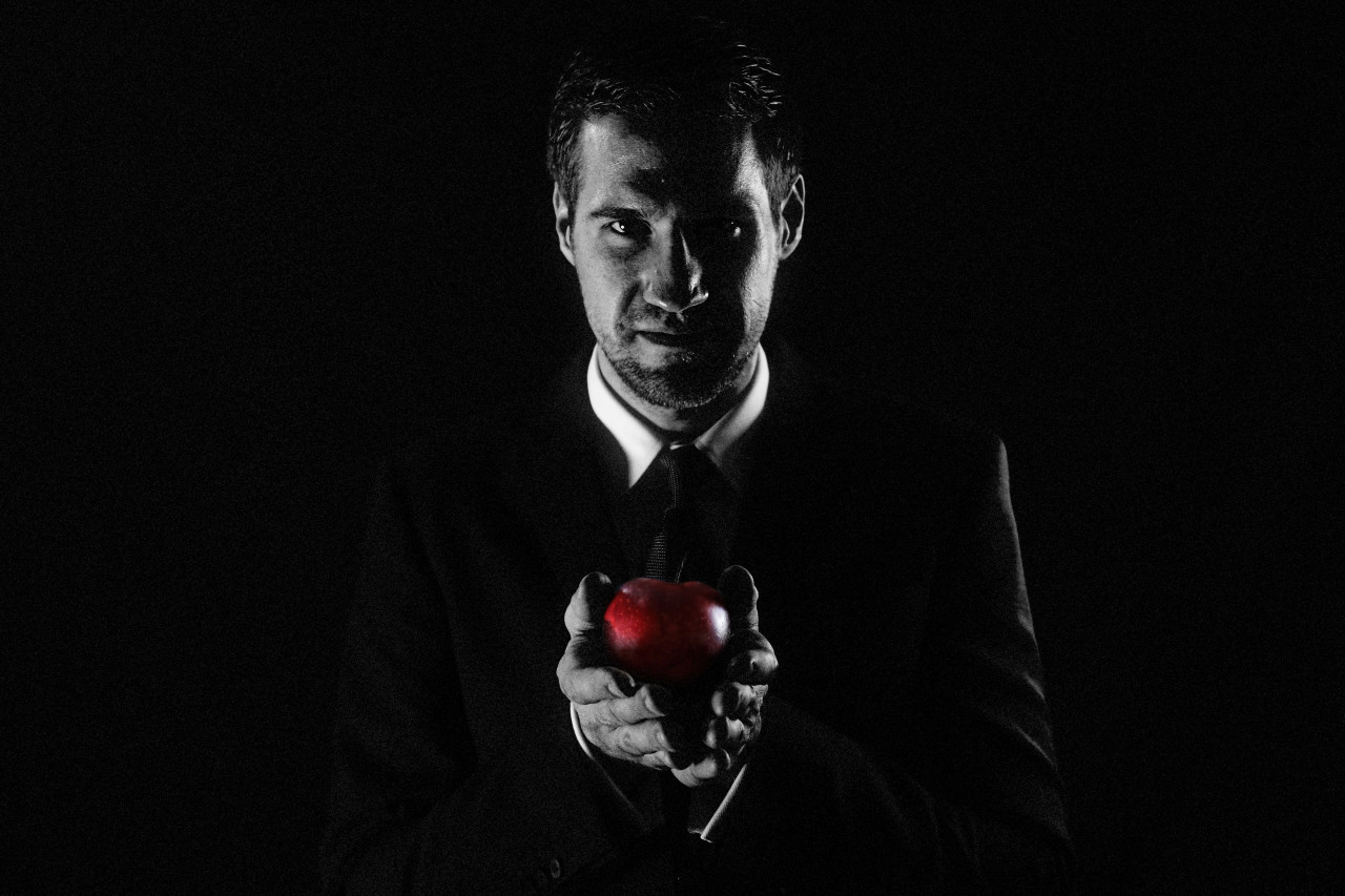 Businessman holds red apple in hand