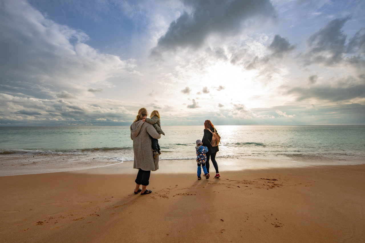 Family with children on the beach in Portugal look into the distance of the sea