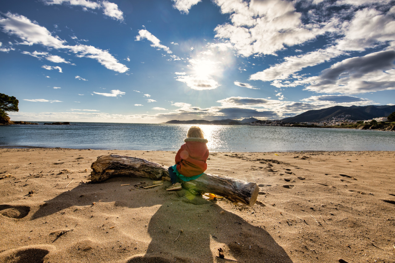 Girl sitting on the beach of Platja Grifeu by Girona in spain