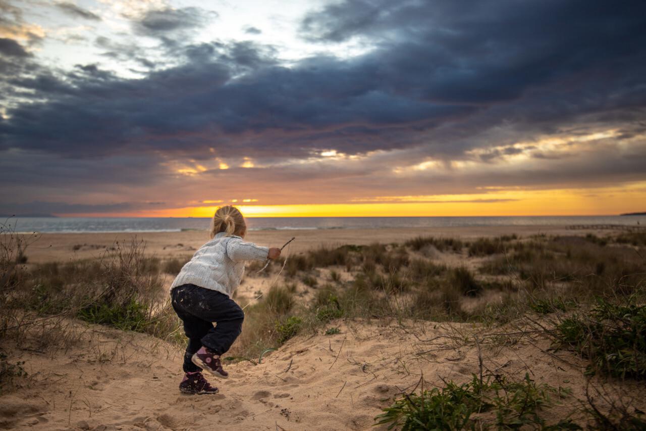 Little girl at sunset on the Spanish beach