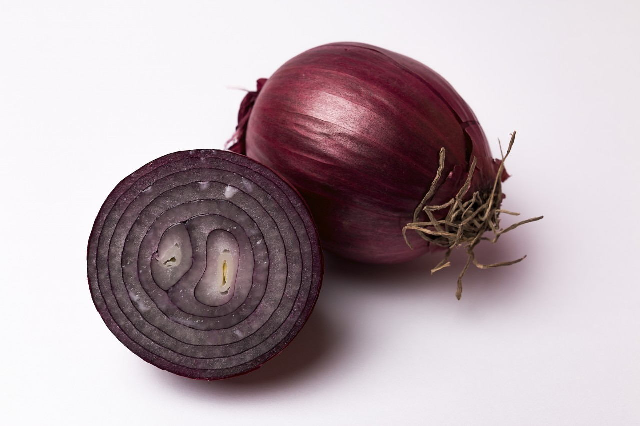 whole and sliced red onion white background