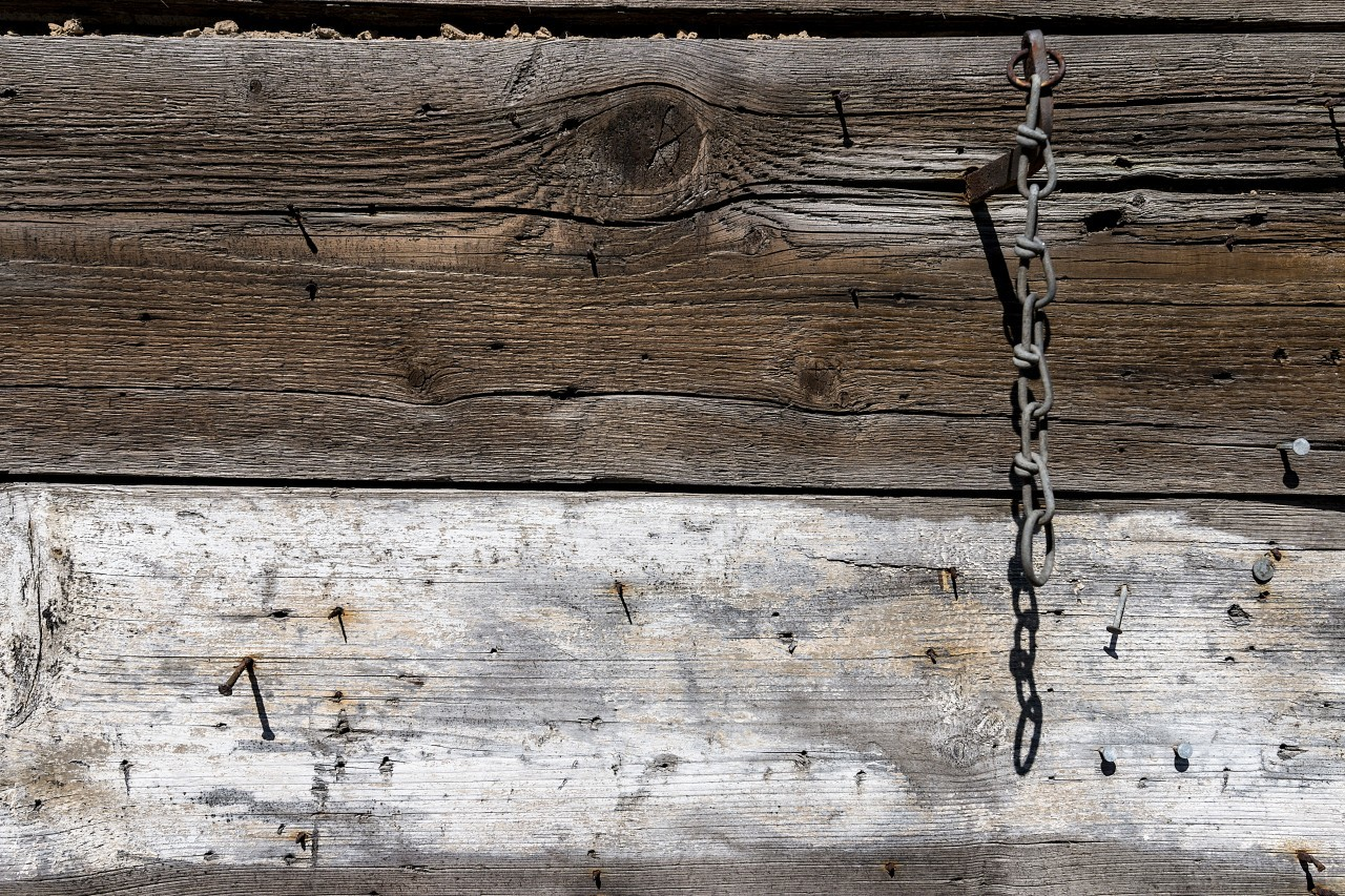 wood wall texture with rusty nails and a chain