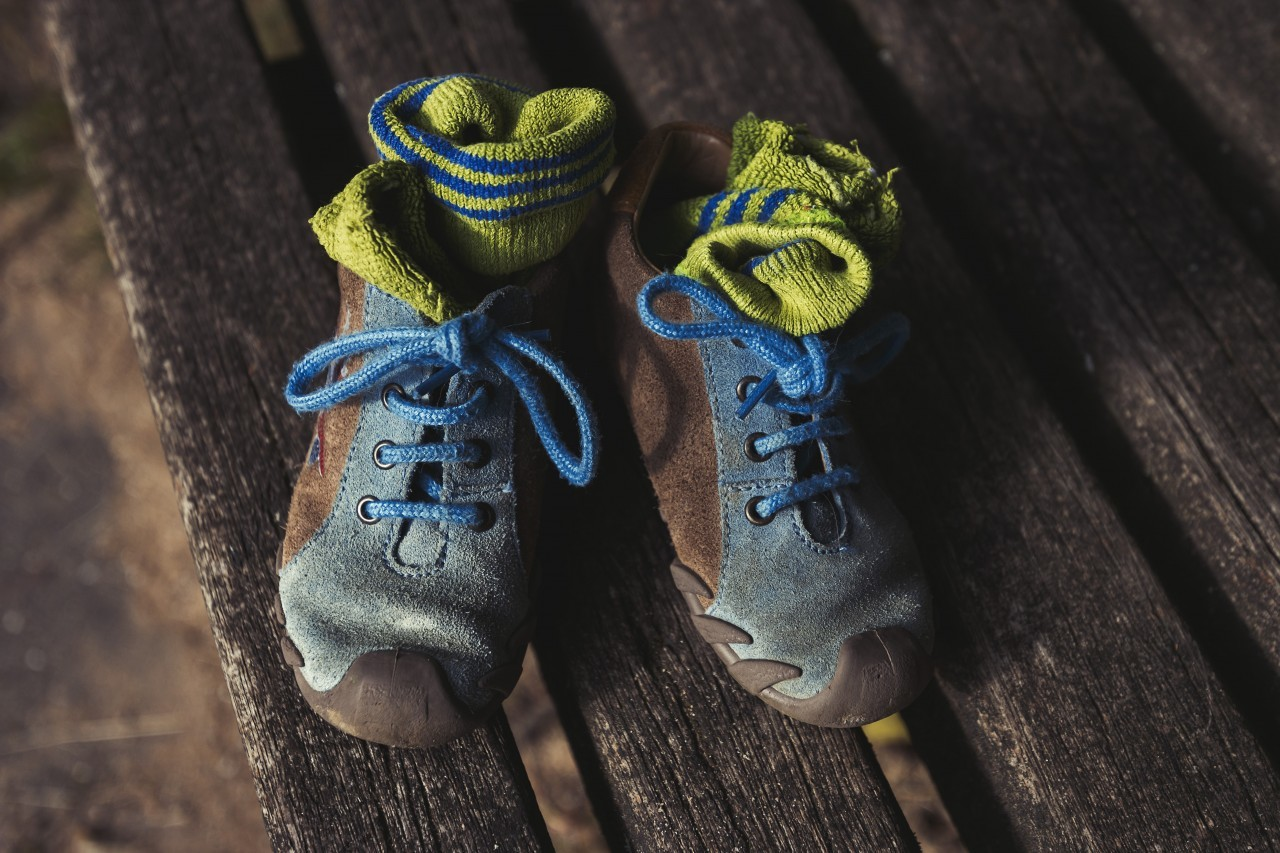 childrens shoes on a park bench topview