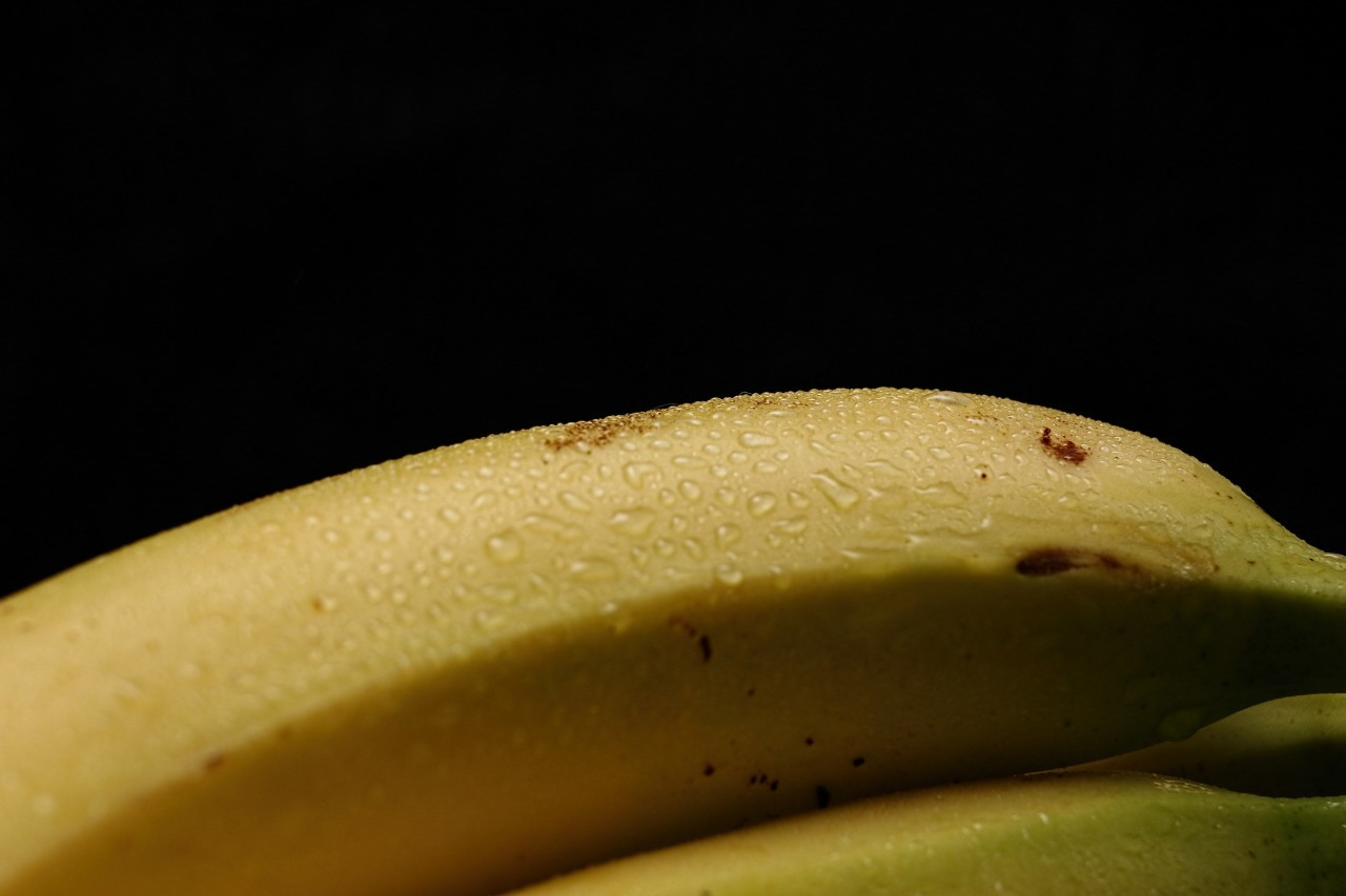 ripe yellow bananas on black background with copy space