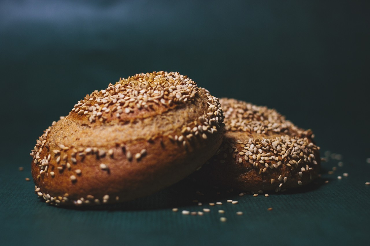 homemade burger rolls sprinkled with sesame seeds on a green background