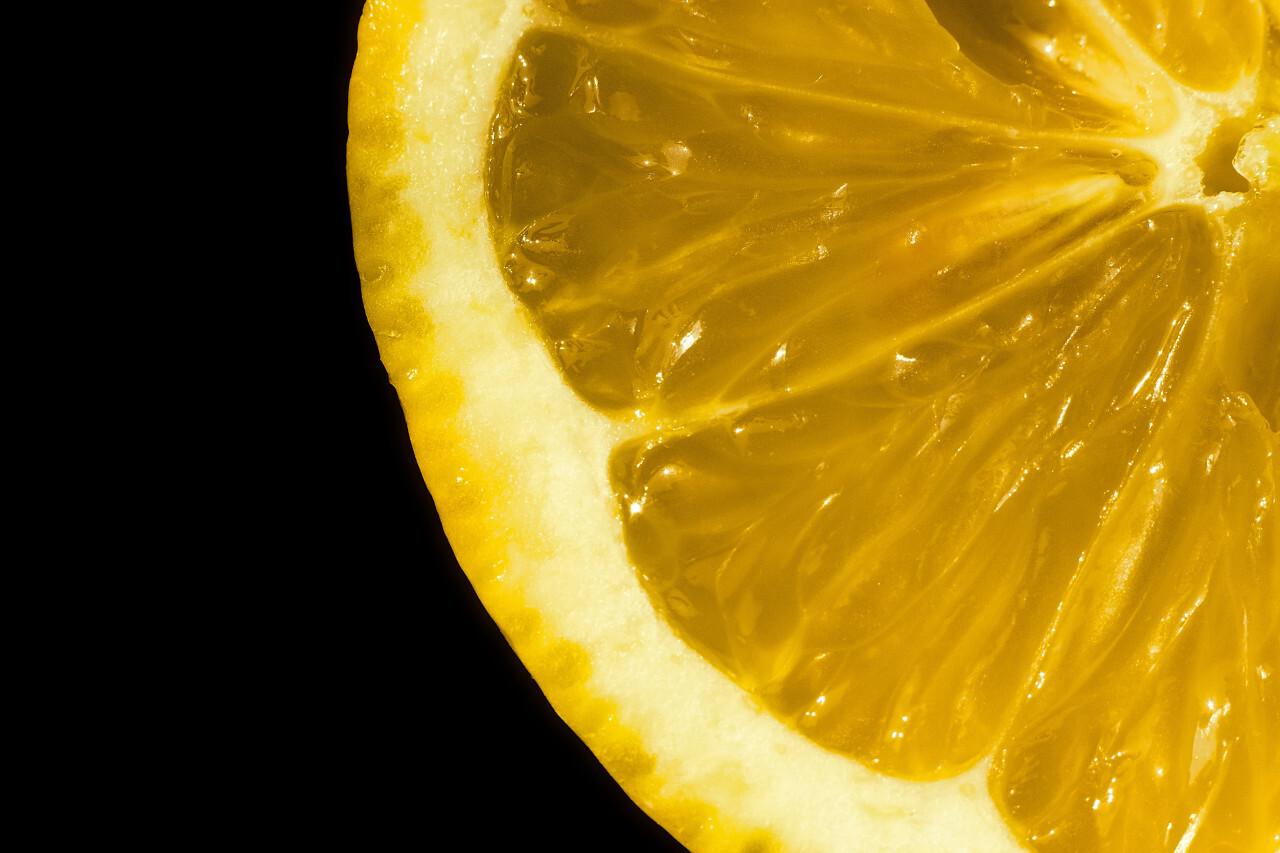Fresh yellow lemon on black background, closeup