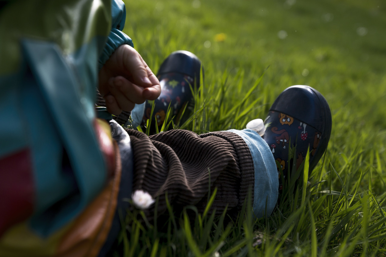 child in rubber boots sits on meadow