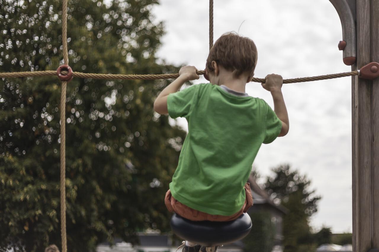 little boy on climbing frame