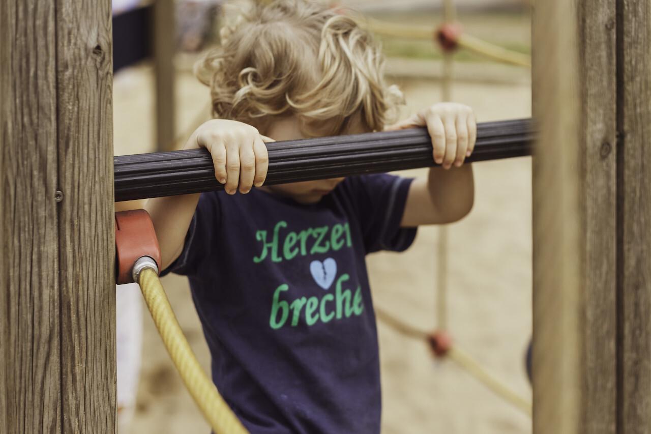 little boy on climbing frame on a playground