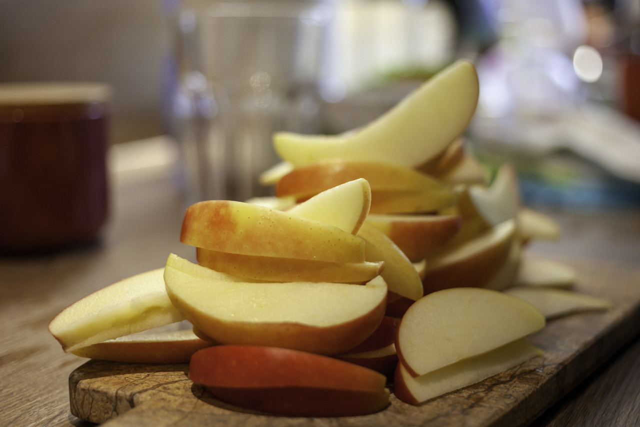 Thin apple slices in a kitchen on a wooden board