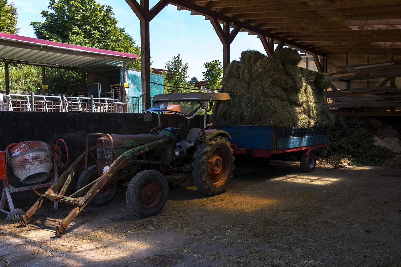 old green tractor with hay loaded trailer