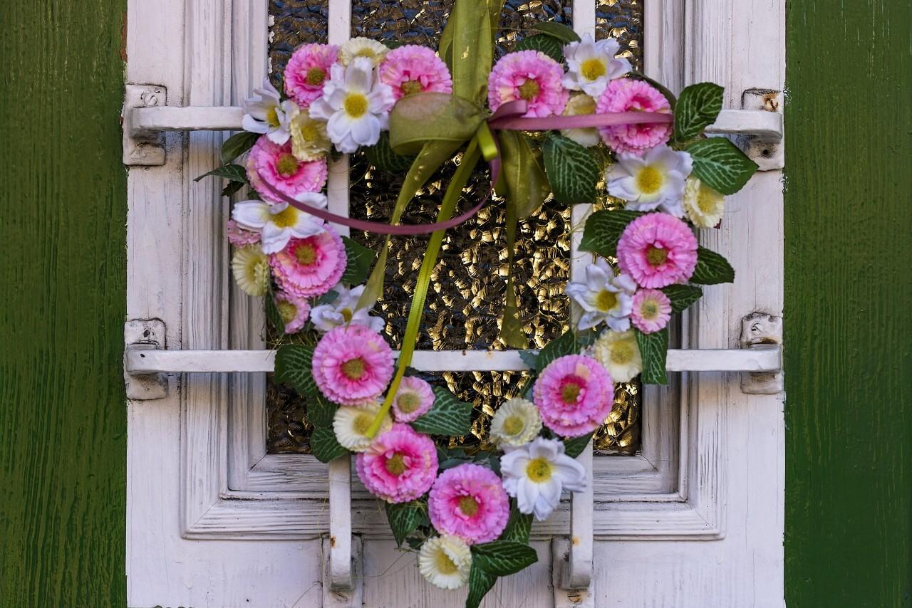 Handmade spring flower wreath on rustic wooden door with velvet material