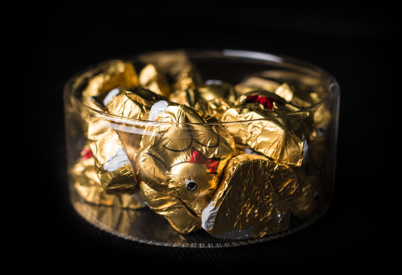 gold wrapped chocolate easter bunny isolated on black background