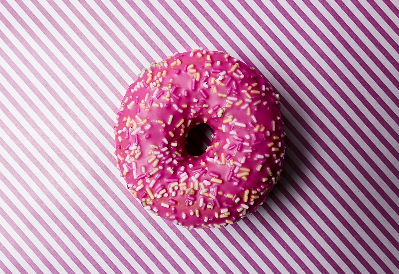 pink frosting donut on pink striped background