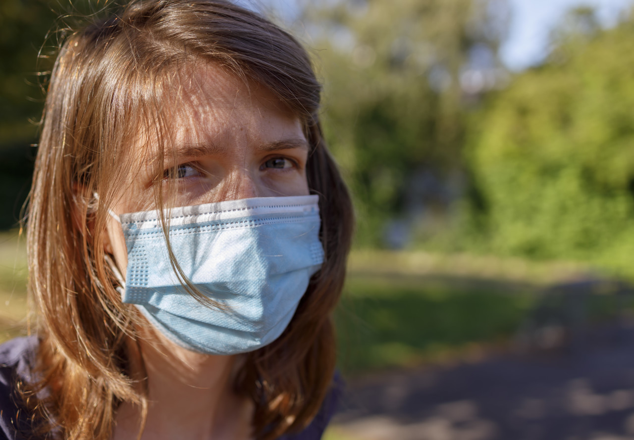 young woman with a mask - protection against covid-19 coronavirus