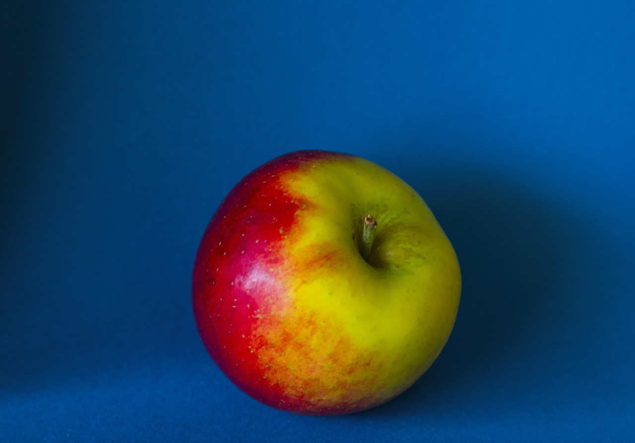 greenish red apple on a blue background