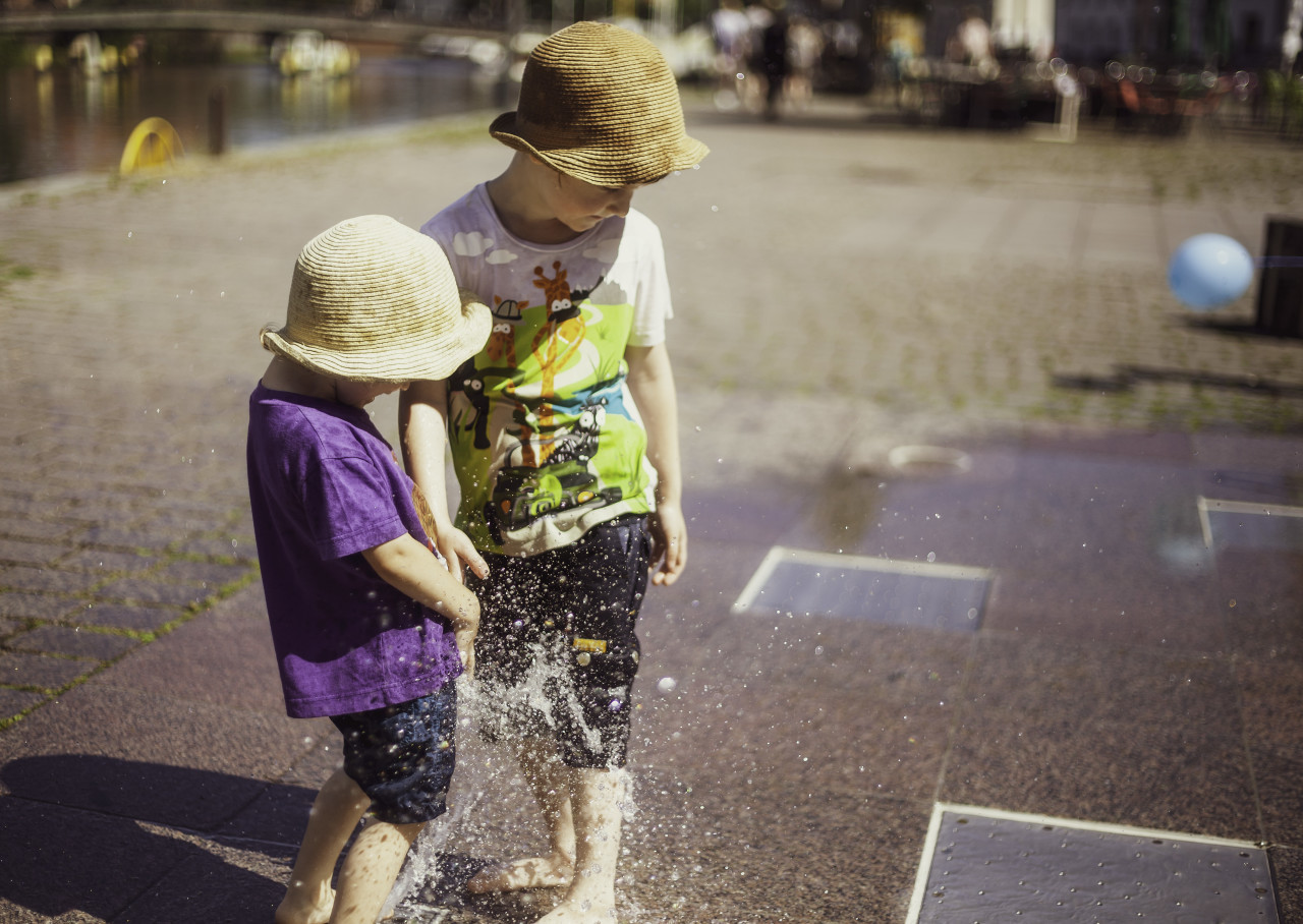 children play at the fountain