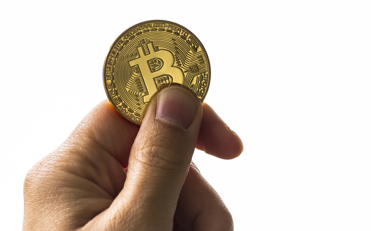 Isolated hand holding a golden bitcoin