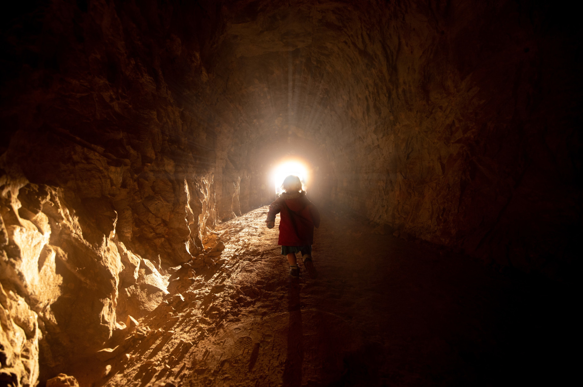 Little girl is running towards the light at the end of the tunnel