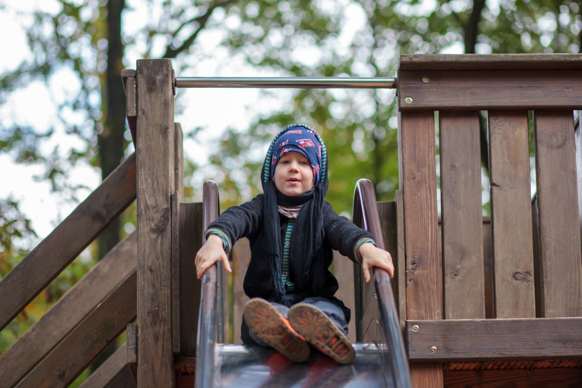 Little boy in autumn on a slide