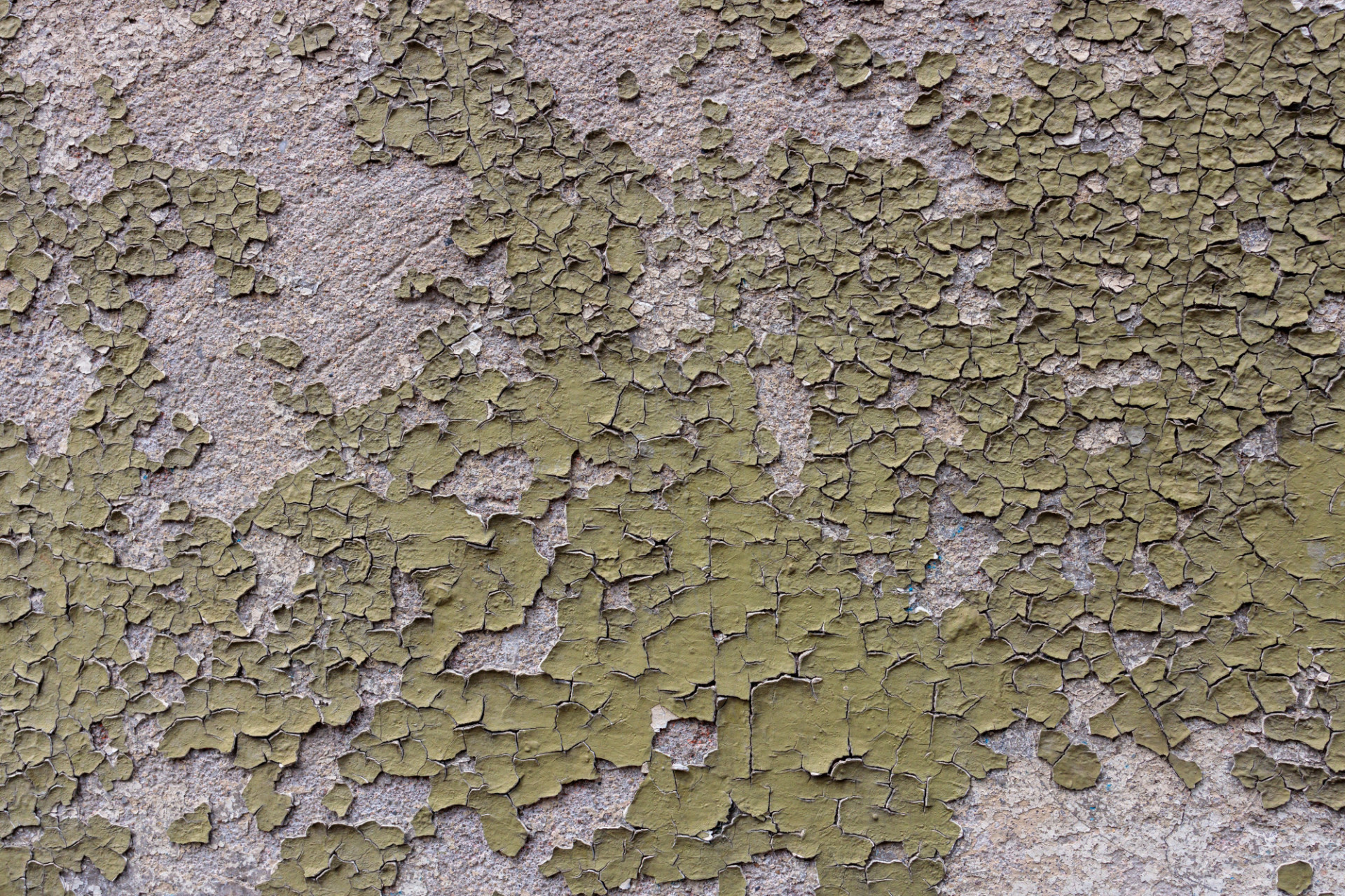 Old wall from which green paint is peeling off