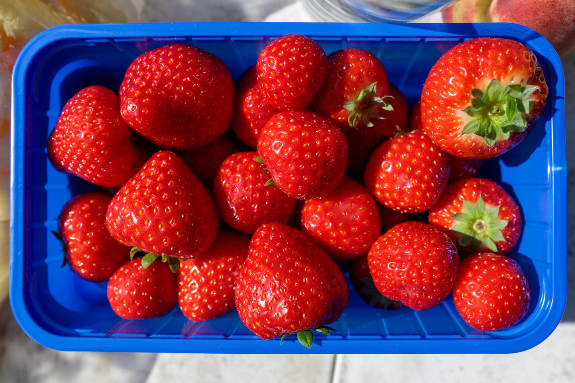 Strawberries from the supermarket in a blue plastic bowl