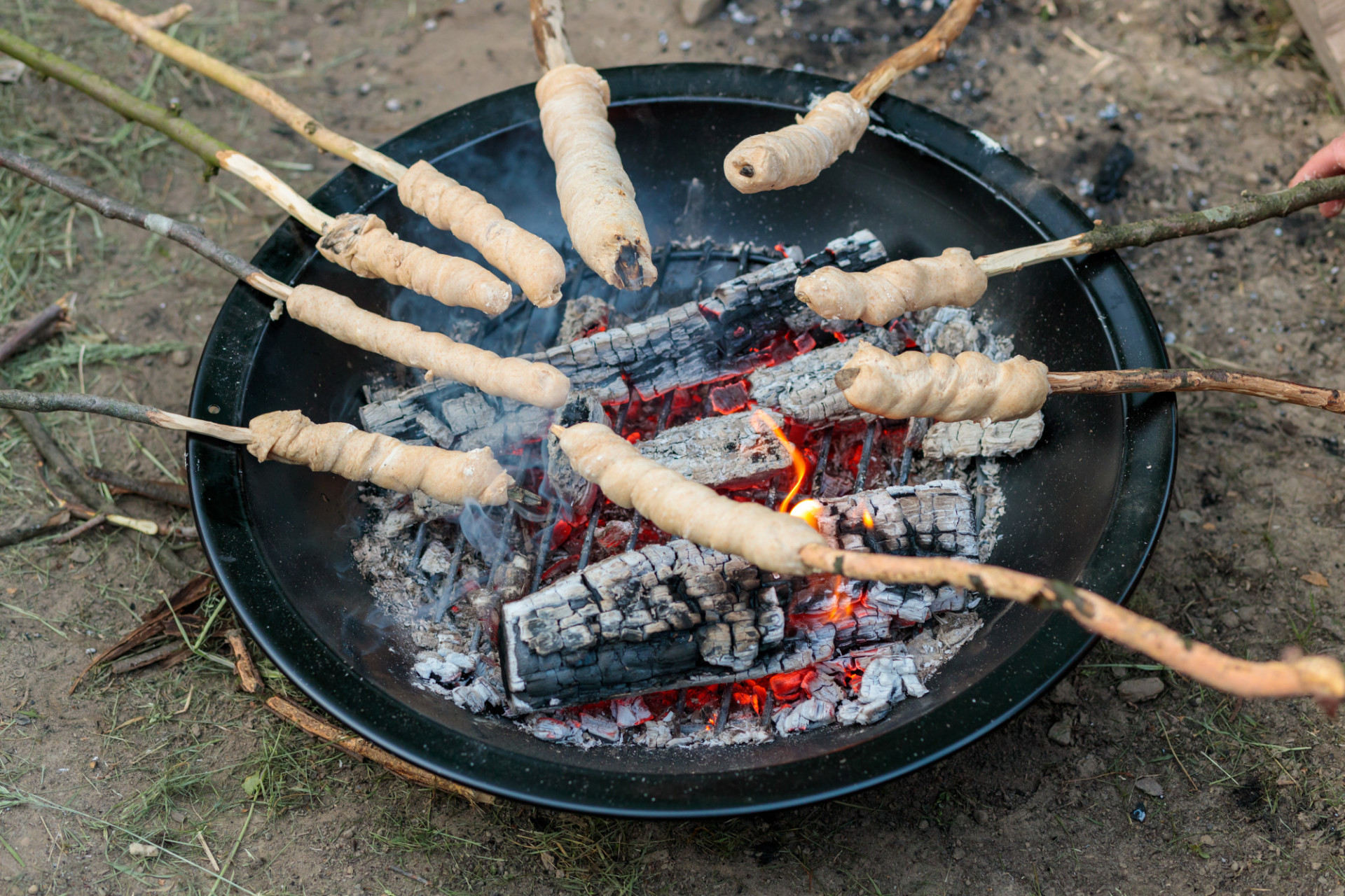 Bread on sticks is grilled over the fire