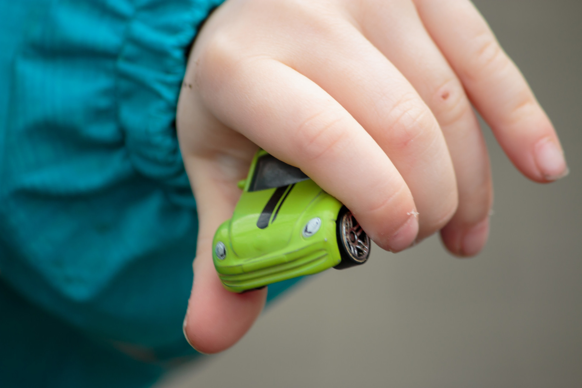 Child holding toy car in hand