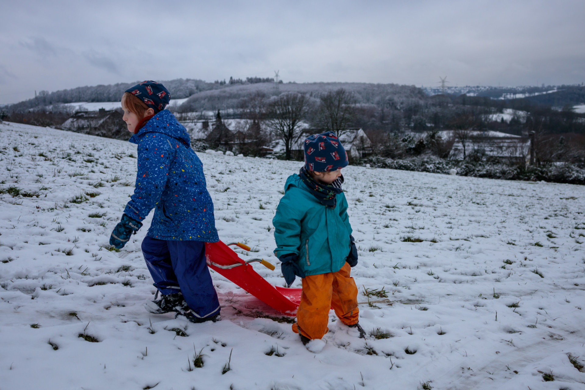 Children pull the sledge up the mountain