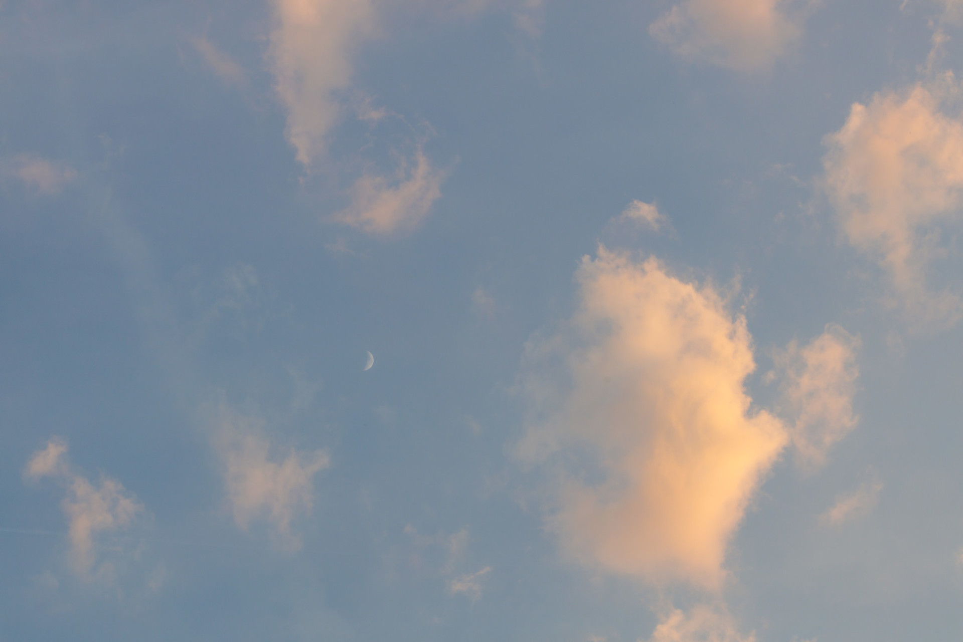 Horizontally photographed sky at evening time with clouds and the moon