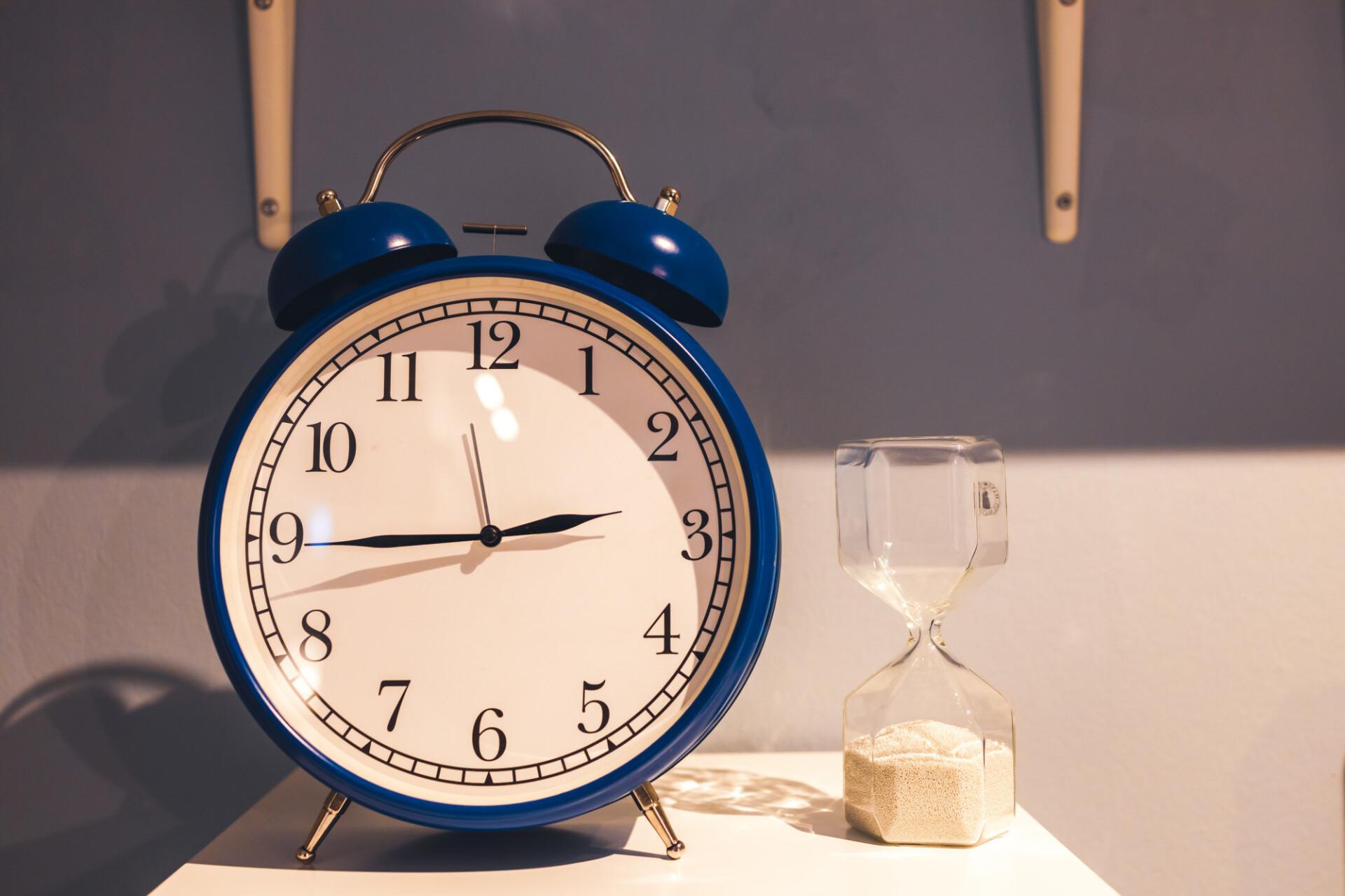 Blue alarm clock and sandglass