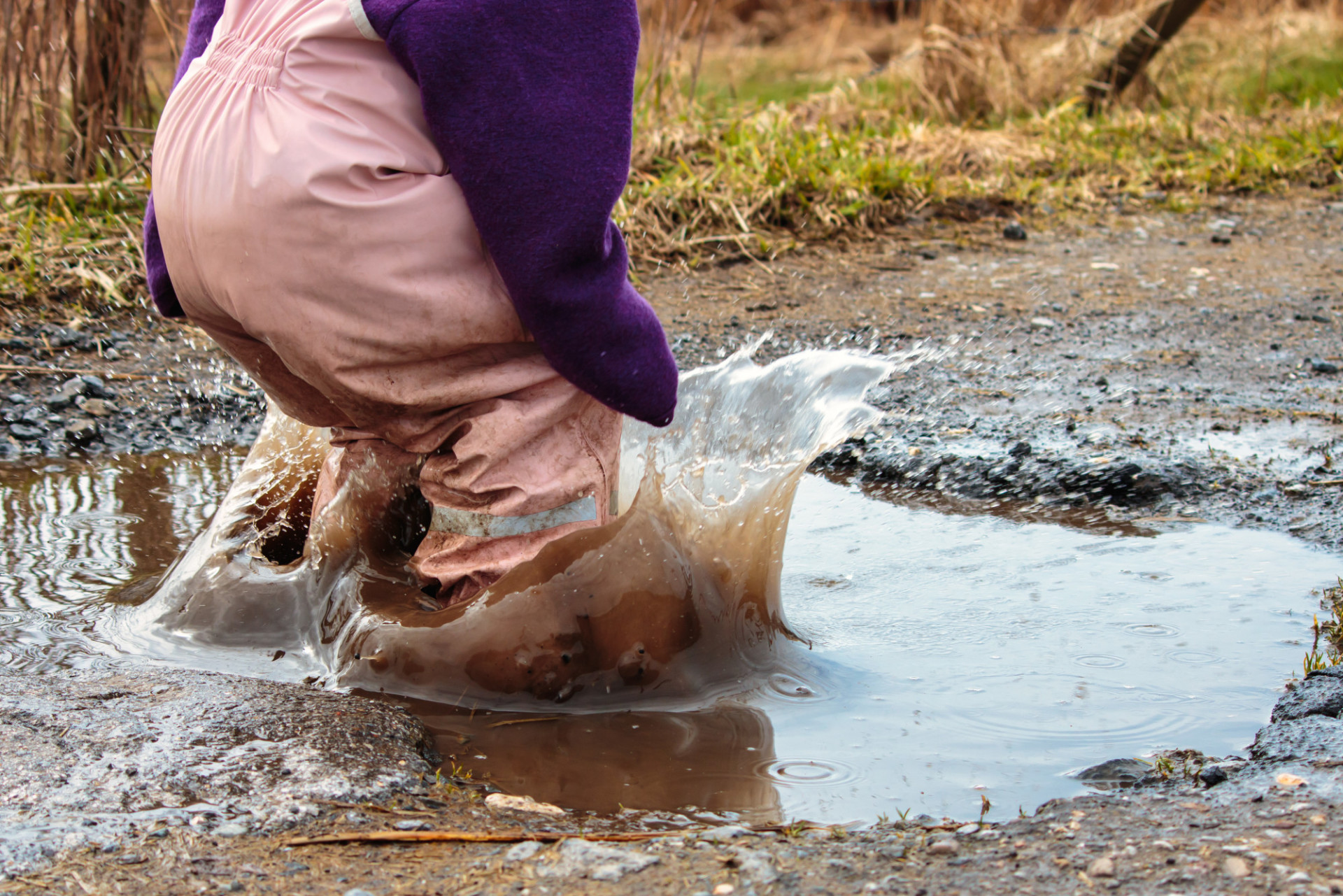 Child jumps into a puddle