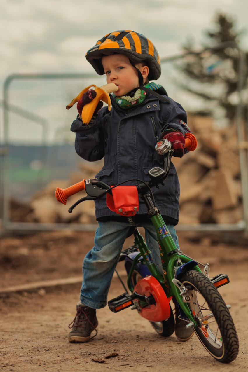Little boy takes a bike break and eats a banana