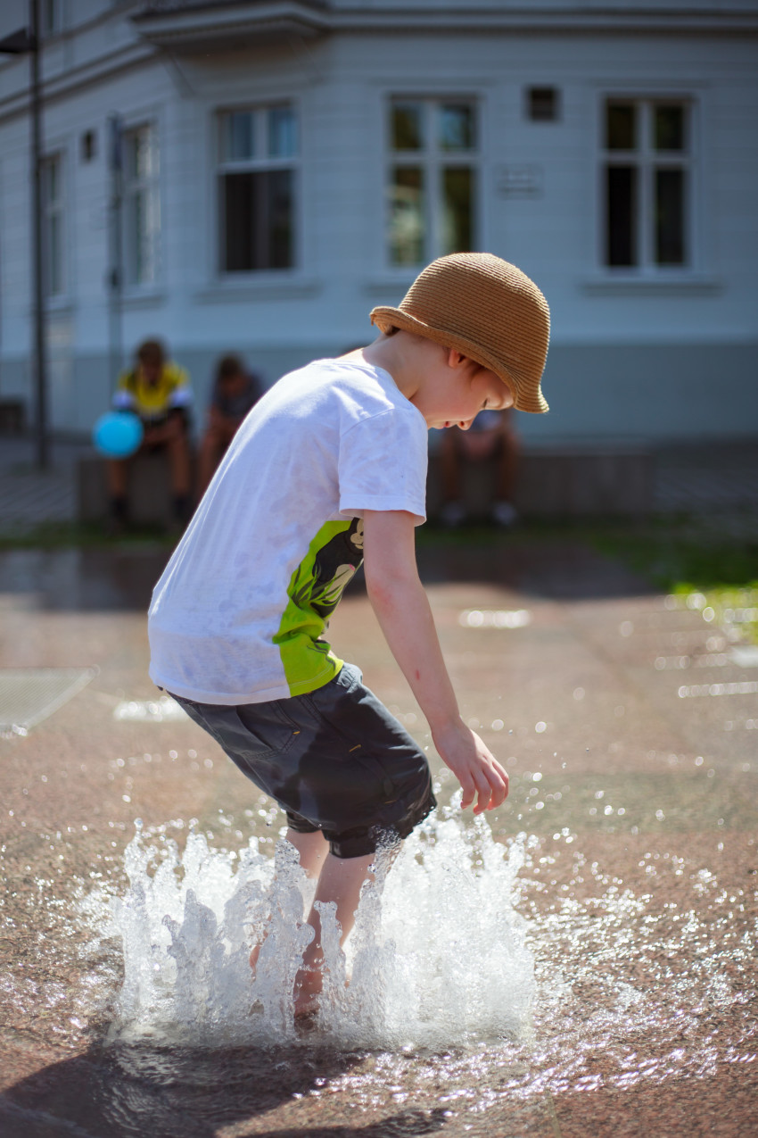 Child plays with the water from a fountain in summer