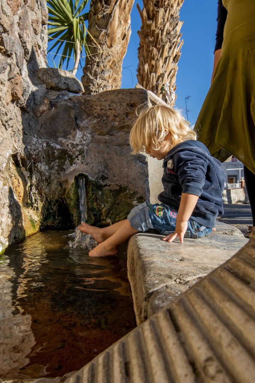 Little girl splashes her feet in a fountain