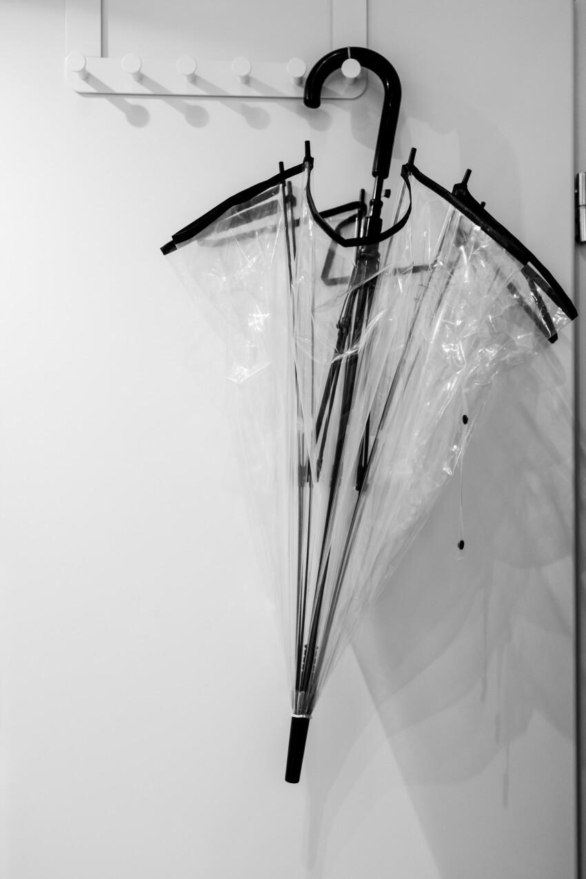 Transparent umbrella hanging on a door