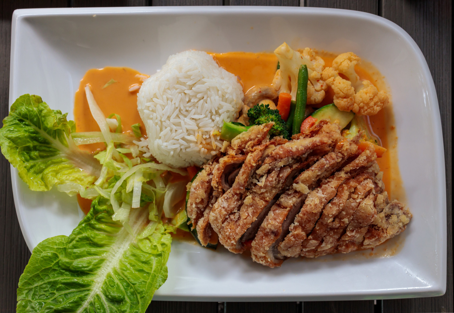 Asian crispy duck with vegetables, rice and curry sauce