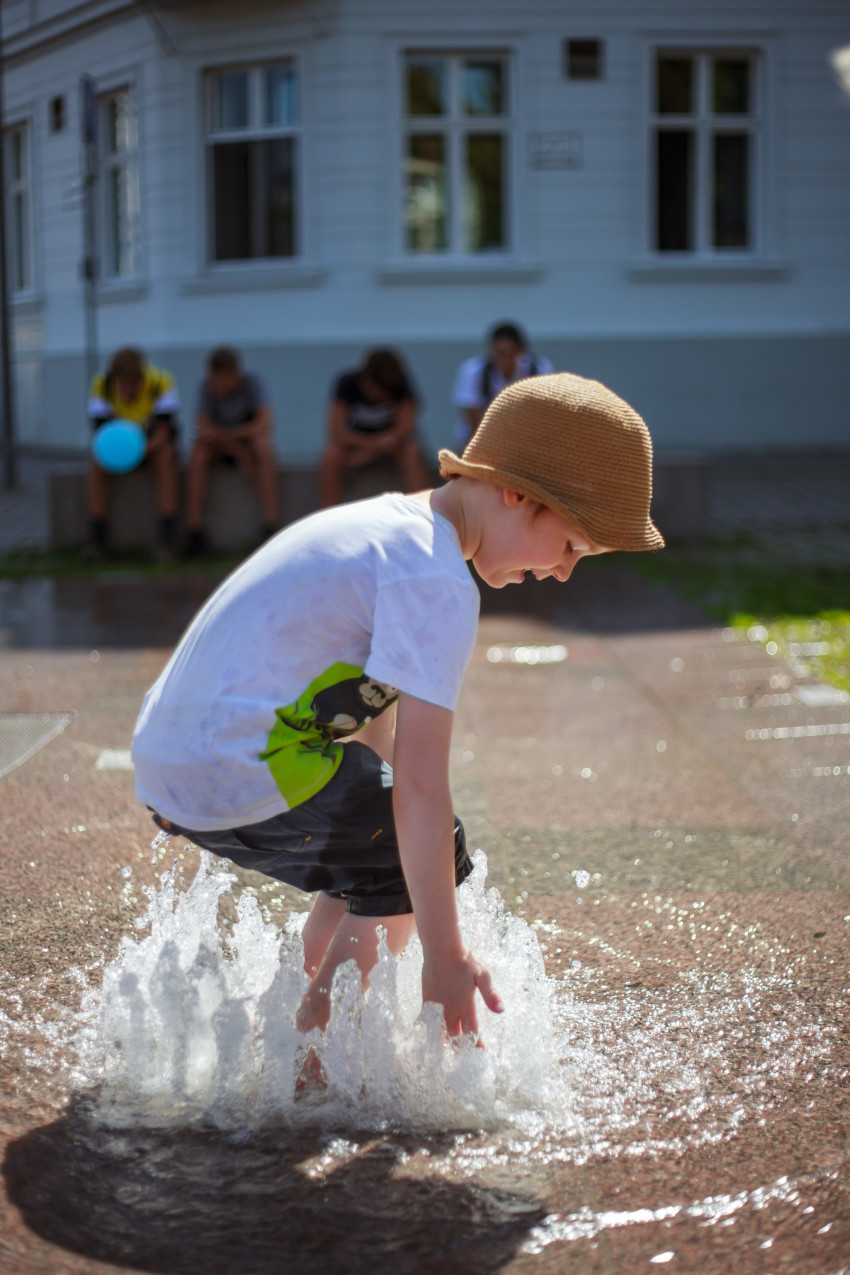 Little Boy plays with the water from a fountain in summer