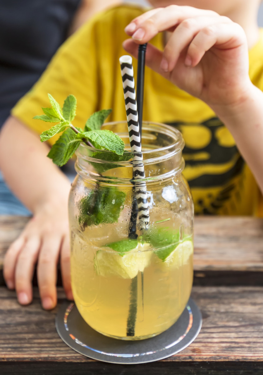 Little Child drink juice or ice tea or summer drink from glasses through straws