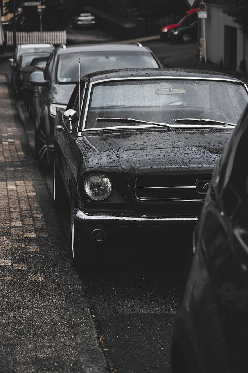 oldtimer ford mustang wet in a parking slot