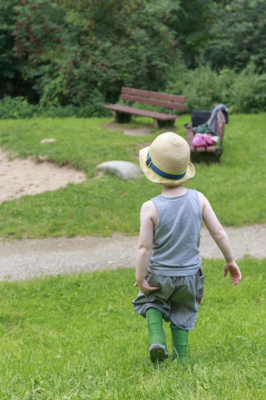 Toddler in rubber boots and with a hat on his head walks across a meadow