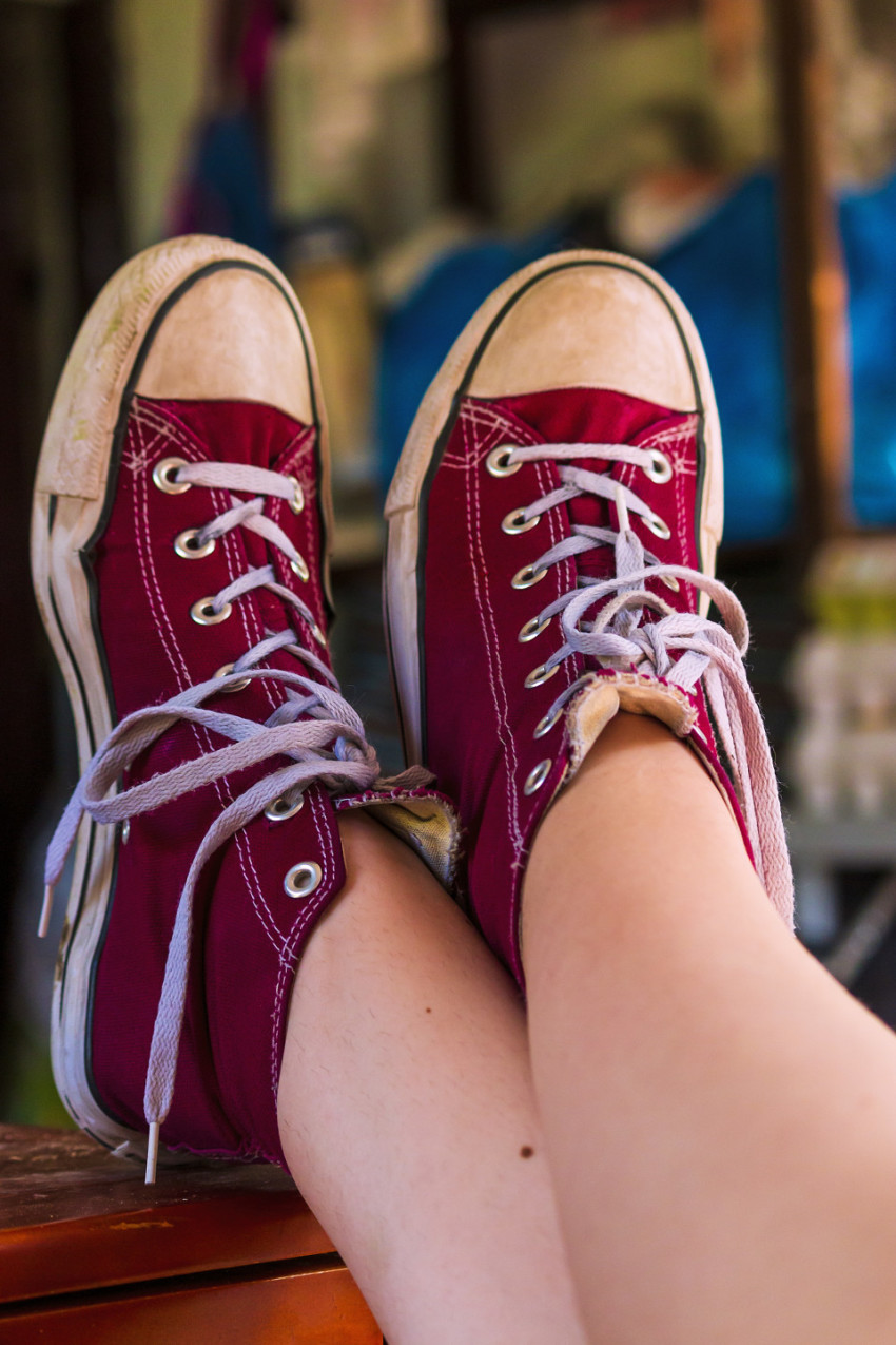 legs of a girl with red chucks