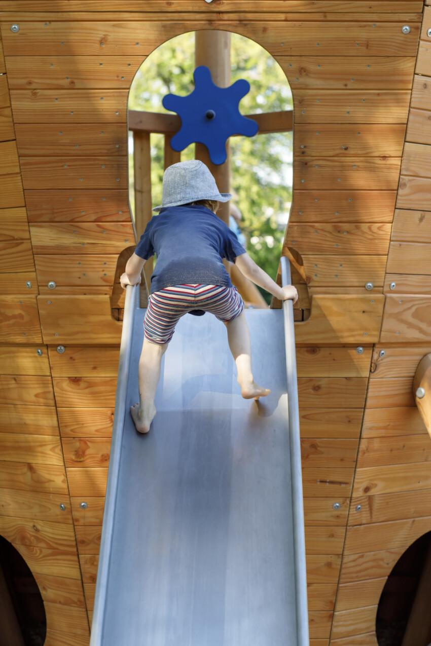 Little boy climbs up a slide on a playground