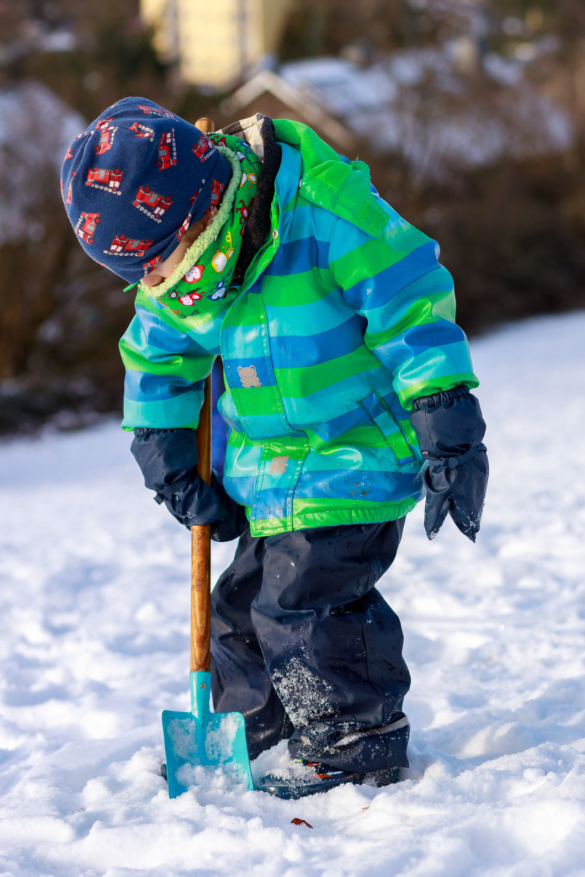 Little boy shovels snow