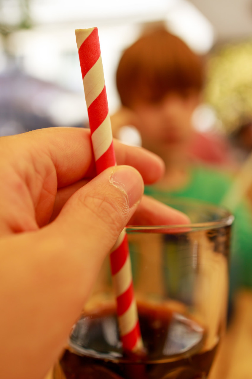 A glass of cola with one hand on the straw
